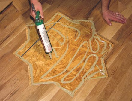 Photo 7: Apply adhesive to the subfloor in a thickness that will match the overall elevation of the floor.